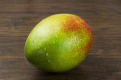 Vida tropical das vitaminas naturais amarelas verdes vermelhas frescas maduras molhadas da manga na madeira Foto de Stock Royalty Free