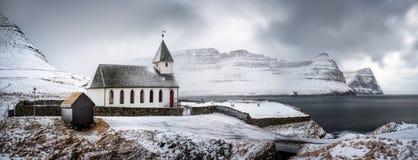 Vidareidi church panorama. White church in snowy Vidareidi village with Bordoy and Kunoy islands in background, Faroe Islands stock photography