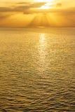 Vidd av havet på soluppgång med solstrålar och moln arkivfoto
