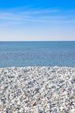 Vidd av vitt grus på havskusten med det lugna havet på backgr arkivbilder