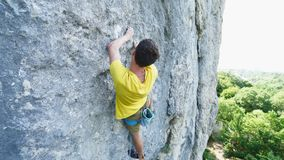 Vide angle view of man rock climber in yellow t-shirt, climbing on a cliff, searching, reaching and gripping hold