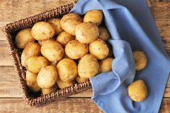 Vide- korg med unga potatisar Arkivbild