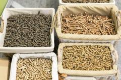 Vide- korgar med olika sorter av pelleted sammansatt matning på jordbruks- utställning Miljövänligt bränsle royaltyfri fotografi