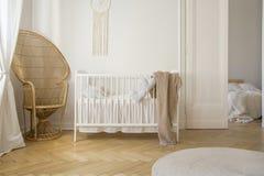 Vide- påfågelstol bredvid vit sängkläder, verkligt foto royaltyfri fotografi