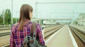 Vide posterior: Una mujer joven apuesta va a lo largo de la plataforma ferroviaria Utiliza un teléfono móvil El concepto es un ac almacen de metraje de vídeo
