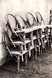 Vide- stolar för klassiskt kafé som staplas mot en vägg Arkivfoto