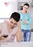 Videira vermelha dos pares infelizes na cozinha Imagem de Stock Royalty Free