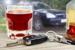 Videl ivre de sujet derrière la roue Clés de voiture avec un verre de boisson alcoolisée sur le fond de la voiture photographie stock libre de droits