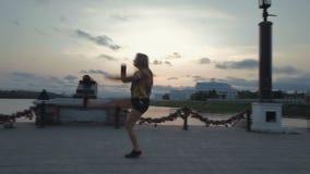 Video acrobatico del metraggio delle azione di tramonto dell'argine di ballo della bella ragazza stock footage