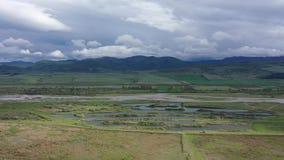 Video aereo Campi e fiume verdi Le montagne sono visibili sull'orizzonte stock footage