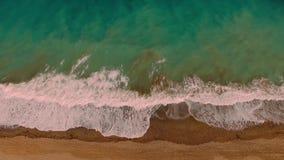 Video aereo del fuco delle onde del mare che raggiungono riva Lockdown delle onde di oceano che creano una struttura dalla schium video d archivio