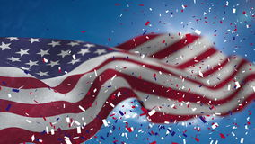 Video of American flag and confetti. With blue sky stock video footage