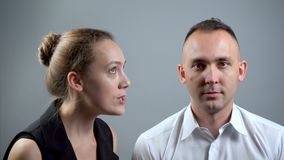 Video of angry girlfriend and man on grey background. Video of man and woman sitting near on grey background stock footage