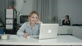 Video appell för ung danande för kvinnlig arbetare via bärbara datorn i kontoret royaltyfri foto