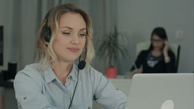 Video appell för ung danande för kvinnlig arbetare via bärbara datorn i kontoret royaltyfria foton