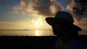 Video Asian girl wearing hat relaxed holiday at golden sunrise ocean beach. Asian girl wearing hat relaxed holiday at golden sunrise ocean beach stock footage