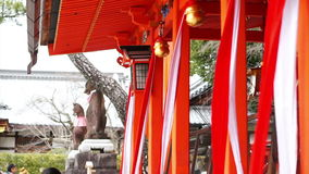 Video Asian Japanese girl praying at red shinto temple with bell stock footage