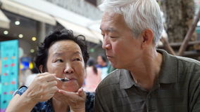 Video Asian senior couple eating an ice cream and feed each other abstract eternal love stock footage