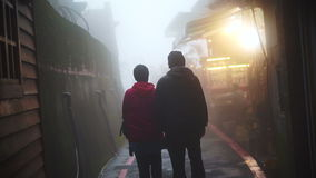 Video Asian senior couple walking and holding hands together in the mist. Travel and see the world together. Asian senior couple walking and holding hands stock video footage
