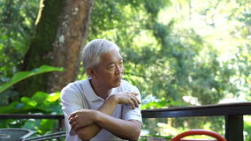 Video Asian senior guy thinking and worry in green lush nature background. Asian senior guy thinking and worry in green lush nature background stock footage