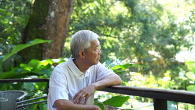 Video Asian senior guy thinking and worry in green lush nature background stock video