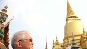 Video Asian senior man visiting Wat Phra Kaew, Temple of the Emerald Buddha Landmark of Bangkok,Thailand stock video