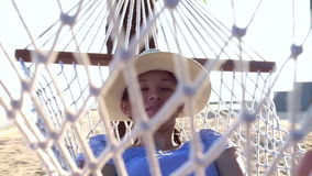 Video Asian woman, girl wearing hat relax on a hammock on the sunny beach with coconut trees stock footage