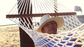 Video Asian woman, girl wearing hat relax on a hammock on the sunny beach with coconut trees stock video footage