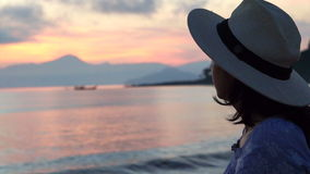Video Asian Woman silhouette with hat Enjoying Seascape during Sunrise. beautiful tropical beaches and landscape stock video footage