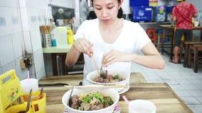Video asiatisk flicka som äter den lokala nudeln i thailändsk restaurang arkivfilmer