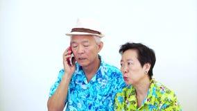 Video av asiatiska höga par som är ilskna på telefonen Rubbning för semester lager videofilmer