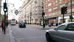 Video av bilar, shoppare, taxi, röda London för dubbel däckare bussar, Oxford gata, London, England arkivfilmer