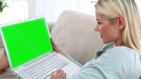 Video av folk som använder en bärbar dator i en vardagsrum stock video