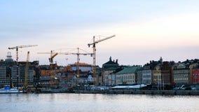 Video av Gamla Stan i Stockholm, Sverige med konstruktionskranar under solnedgången stock video