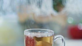 Video avvolto senza cuciture con un vetro di cottura a vapore del tè caldo su una tavola video d archivio