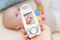 Video baby monitor for security of the baby. Hand holding video baby monitor for security of the baby Royalty Free Stock Images