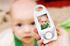Video baby monitor for security of the baby. Hand holding video baby monitor for security of the baby Stock Photos