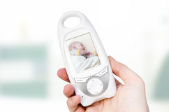 Video baby monitor for security of the baby. Hand holding video baby monitor for security of the baby Royalty Free Stock Image