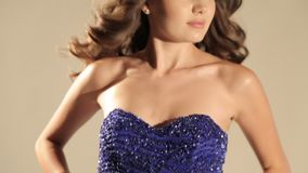 Beautiful woman with dark hair in luxurious dress and precious crown posing in studio. Video of beautiful woman with dark hair in luxurious dress and precious stock footage