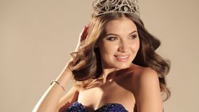 Beautiful woman with dark hair in luxurious dress and precious crown posing in studio stock video