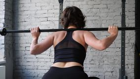 This video is about Beautiful young athletic sporty woman doing back squat cardio workout in gym. Back close up view stock video footage