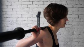 This video is about Beautiful young athletic sporty woman doing back squat cardio workout in gym. Front close up view stock footage