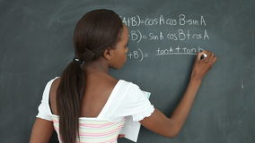 Video of a black student writing on a blackboard stock video