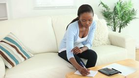 Video of a black woman using a calculator. In a living room stock video footage