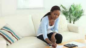 Video of a black woman using a calculator. In a living room stock footage