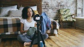 Video blog sorridente della registrazione afroamericana riccia della ragazza circa il suo guardaroba per il viaggio con la macchi video d archivio