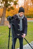 The videoblogger adjusts his camera amid the park Stock Images