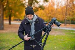 The videoblogger adjusts his camera, tripod Royalty Free Stock Photos