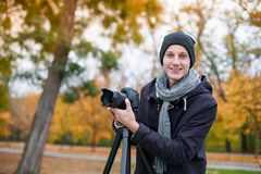 The videoblogger smilling adjusts his camera Royalty Free Stock Photo