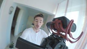 Video blogger dell'adolescente maschio che cammina in ogni stanza a casa con una macchina fotografica mobile e che presenta la su video d archivio